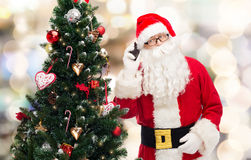 Santa claus with smartphone and christmas tree. Holidays, technology and people concept - man in costume of santa claus with smartphone and christmas tree over royalty free stock photo