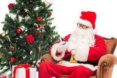 Santa claus with smartphone and christmas tree Royalty Free Stock Photos