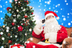 Santa claus with smartphone and christmas tree. Holidays, technology and people concept - man in costume of santa claus with smartphone, presents and christmas royalty free stock image