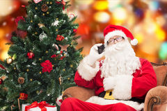 Santa claus with smartphone and christmas tree. Holidays, technology and people concept - man in costume of santa claus with smartphone, presents and christmas stock photos