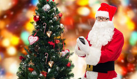 Santa claus with smartphone and christmas tree Stock Photo
