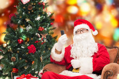 Santa claus with smartphone and christmas tree Royalty Free Stock Photo