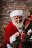 Santa Claus Smiling by the Christmas Tree. Santa Claus smiling as he is sneaking around the Christmas Tree Stock Photo