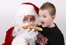 Santa claus smiling and eating pizza Royalty Free Stock Images