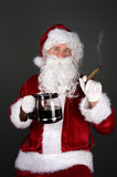 Santa Claus smoking a cigar and drinking coffee Stock Images