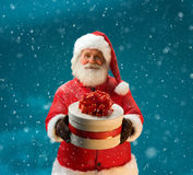 Santa Claus in snowfall with gifts to children. Royalty Free Stock Photo