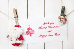 Santa Claus and snowman clothespin holding Christmas greeting ca Stock Image