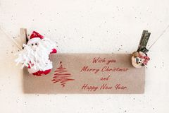 Santa Claus and snowman clothespin holding Christmas greeting ca Stock Photography