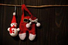 Santa Claus and snowman haning on dark wood wall royalty free stock photos