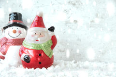 Santa claus with snowman and snowfall Stock Images