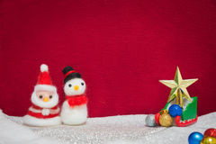 Santa claus, snowman wool doll, green sled on snow set up with g Stock Images