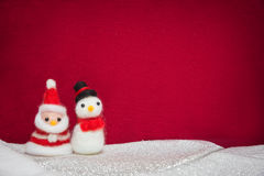 Santa claus, snowman wool doll on snow set up with red cloth bac Royalty Free Stock Images