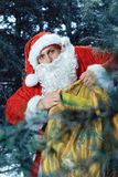 Santa claus . new yaer and christmas. Santa Claus in a snowy forest with a bag of presents and a stick in his hands royalty free stock photo