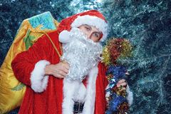 Santa claus . new yaer and christmas. Santa Claus in a snowy forest with a bag of presents and a stick in his hands stock image