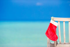 Santa Claus Sock on chair near tropical beach with turquoise sea water and white sand. Christmas vacation concept. Santa hat on chair longue at tropical royalty free stock photography