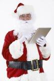Santa Claus som använder den digitala minnestavlan på vit bakgrund Royaltyfria Bilder