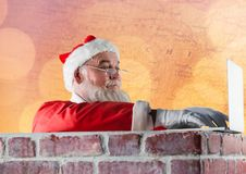 Santa Claus som använder en bärbar dator Arkivbilder