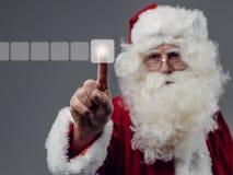 Santa Claus som använder en pekskärmanvändargränssnitt Arkivfoto