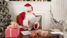Santa Claus som använder minnestavlan för att ge en snabb video appell till nordpolen Royaltyfri Foto