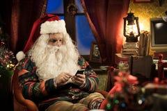 Santa Claus som använder smartphonen Fotografering för Bildbyråer