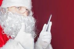 Santa Claus som använder en mobiltelefon på jultid Arkivfoto