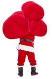 Santa Claus som bär den tunga gåvapåsen Royaltyfri Foto