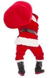 Santa Claus som bär den tunga gåvapåsen Fotografering för Bildbyråer
