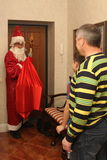 Santa Claus som bär en påse av gåvor och hans personal, gick till lägenheten hälsar mannen, pojke Arkivbilder
