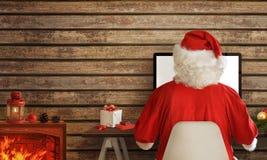Santa Claus som direktanslutet shoppar på datoren från hans varma rum Royaltyfri Bild