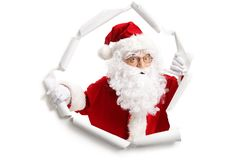 Santa Claus som dyker upp från ett pappers- hål royaltyfria bilder