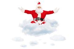 Santa Claus som fördelar hans händer och flyger på moln Arkivbild