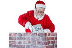 Santa Claus som förlägger gåvaasken in i en lampglas Arkivbild