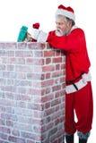 Santa Claus som förlägger gåvaasken in i en lampglas Royaltyfri Fotografi