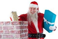 Santa Claus som förlägger gåvaasken in i en lampglas Arkivbilder