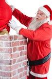 Santa Claus som förlägger gåvaasken in i en lampglas Arkivfoton