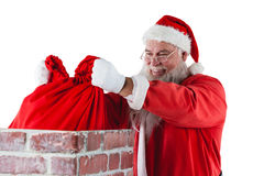Santa Claus som förlägger gåvaasken in i en lampglas Royaltyfria Bilder