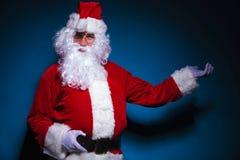 Santa Claus som framlägger på blå backgrorund Arkivbild