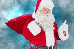 Santa Claus som går med säcken och klockan mot julbakgrund Arkivbilder