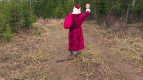 Santa Claus som går och, säger farväl till skogen stock video