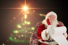 Santa Claus som gör en lista av gåvor Fotografering för Bildbyråer