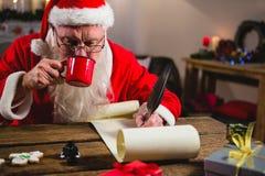 Santa Claus som har kaffe, medan skriva på snirkel Royaltyfri Foto
