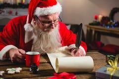 Santa Claus som har kaffe, medan skriva på snirkel Royaltyfria Bilder
