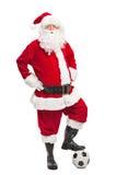 Santa Claus som kliver över en fotboll Arkivfoton