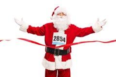 Santa Claus som korsar mållinjen av ett lopp Royaltyfri Fotografi
