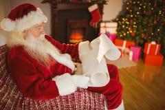 Santa Claus som läser hans lista på jul Royaltyfri Foto