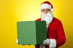 Santa Claus som levererar den stora gröna gåvaasken arkivfoto