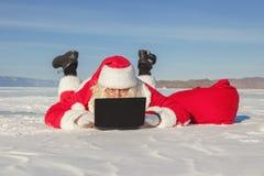 Santa Claus som ligger på snön som ser bärbar datornyheterna Royaltyfria Foton