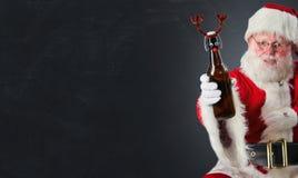 Santa Claus som lyfter ett julrostat bröd med en flaska av öl som dekoreras med hjorthorn på kronhjort över grå färger med kopier arkivbilder