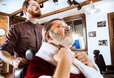 Santa Claus som rakar hans personliga barberare Royaltyfri Foto