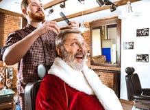 Santa Claus som rakar hans personliga barberare Royaltyfri Bild